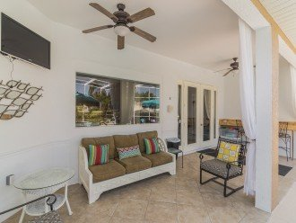 COVERED LANAI WITH OUTDOOR TV & BREAKFAST BAR. 3 LARGE AL FRESCO DINING TABLES.