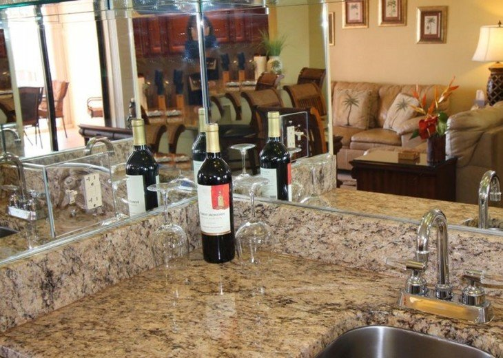 Matching granite counter wet bar next to dining / living areas at your disposal.