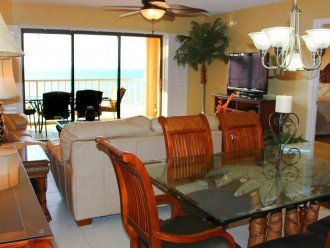 Direct view to Gulf from kitchen counter - glass dining table and living room.
