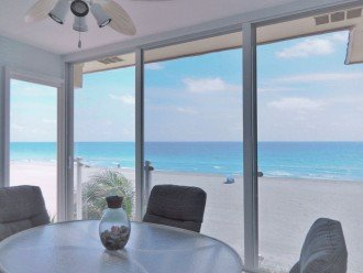 Large beachfront Lanai with floor to ceiling sliding glass panels & glass rail