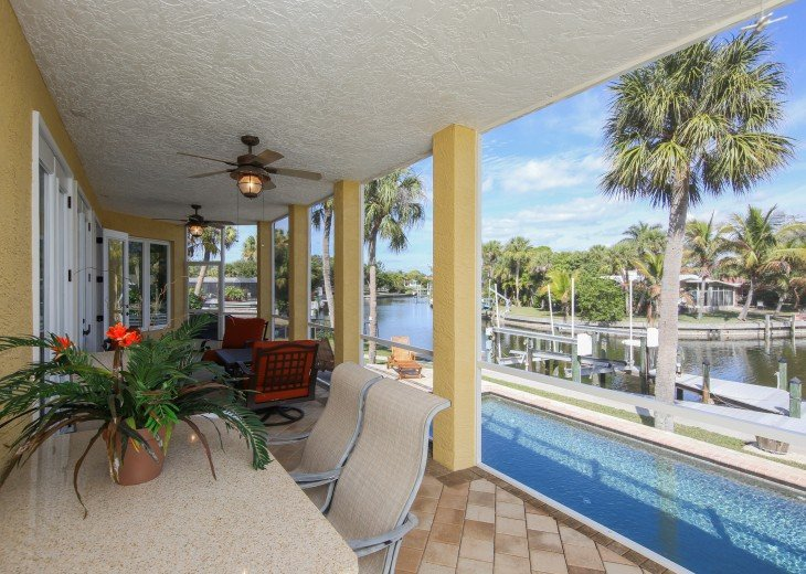 Screened lanai with table and outside living room set, french doors open.