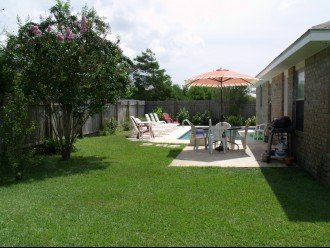 Another view of patio/pool with flowering trees