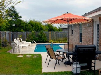 View of patio with gas BBQ grill, picnic table/umbrella, swimming pool