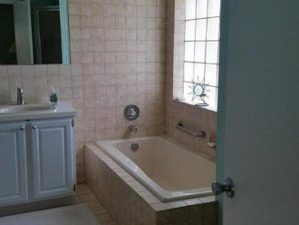 Large soaking tub under block window + corner glass shower stall/robe hooks NIP!