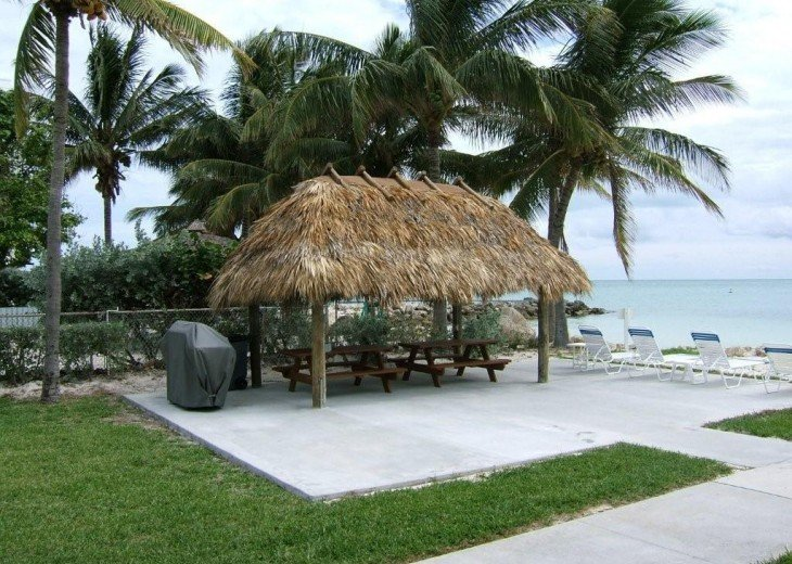 tiki hut by the beach with grills and benches