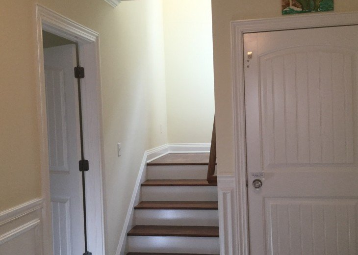 stairs from entrance next to elevator and ground floor bedroom and bath
