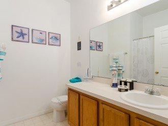 Shared twin bathroom with over bath shower