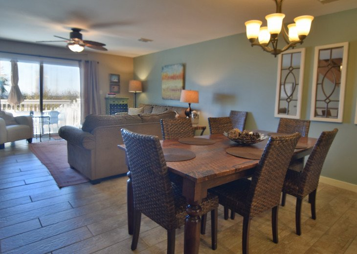 Living area with large dining table that can seat up to 8 with nearby bench.
