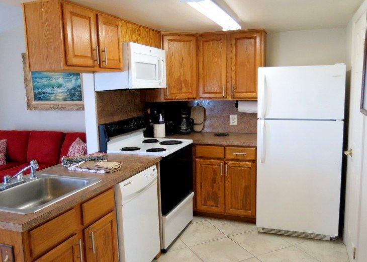 Range, dishwasher, fridge, microwave, silverware, dishes and cooking utensils.
