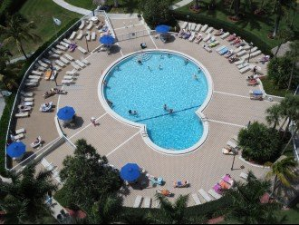 Heated Swimming pool with many chairs just off the side door of 1st floor