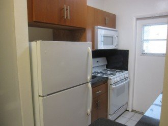 Full kitchen with stove, microwave and fridge
