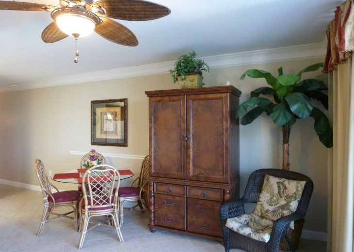 "TV armoire with 32"" TV and wicker chair"