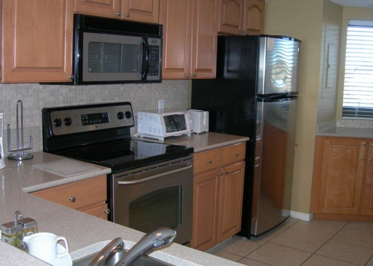 Full size kitchen featuring refrigerator w/ ice maker, oven, microwave, toaster