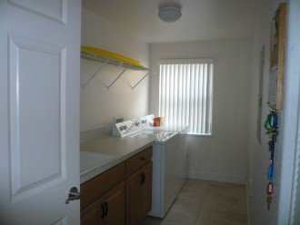 Units laundry room with cabinets and utility sink and window.