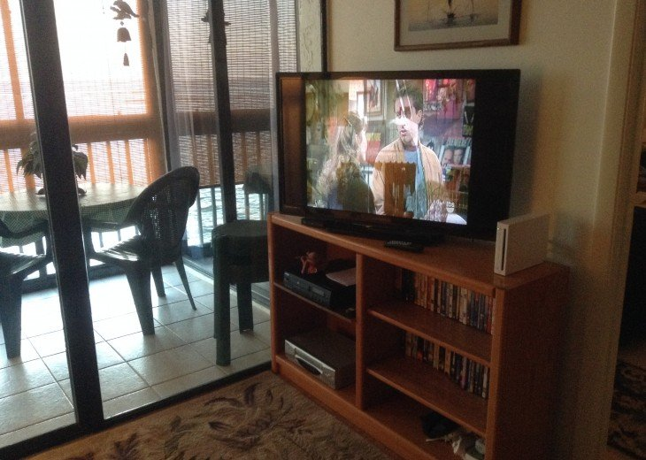 Living room with large flatscreen TV, games, books, videos.....