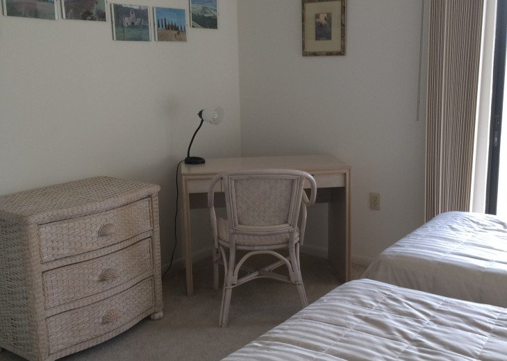 guest room with rattan desk and chest of drawers