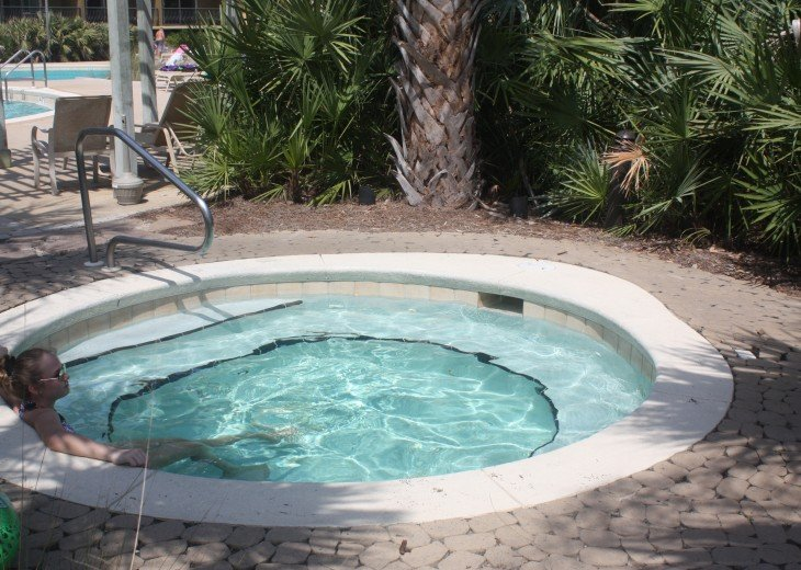Heated spa (hot tub) next to pool with tropical landscaping