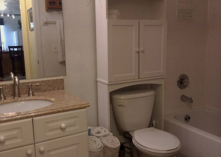 Studio full bath with shower/bath combo, granite counter, storage cabinet