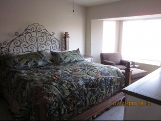 Master bedroom with King bed, chair, dresser, walk in closets, bath/shower