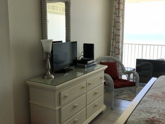 flat screen cable tv in master bedroom along with sliding doors to balcony.
