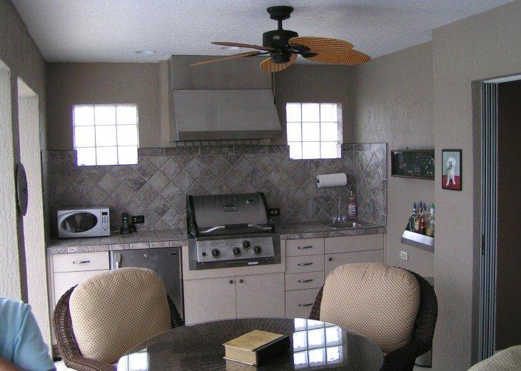 Summer kitchen with gas grille, sink, and refrigerator
