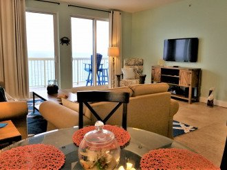 View from the dining table towards the main living area, gulf views & mounted TV