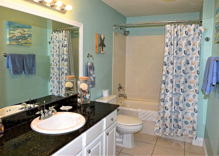 Guest bath has large vanity w/ extra storage & a tub/shower combo