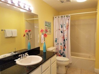 Guest bath has large vanity w/ extra storage & tub-shower combo