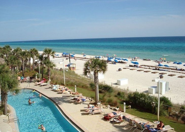 View of 1 of 2 beach side pools with the warm white sand & Gulf all in one shot