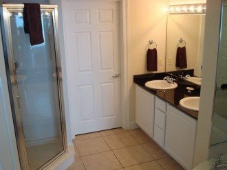 En suite has walk in shower & dual vanity sinks with extra storage underneath