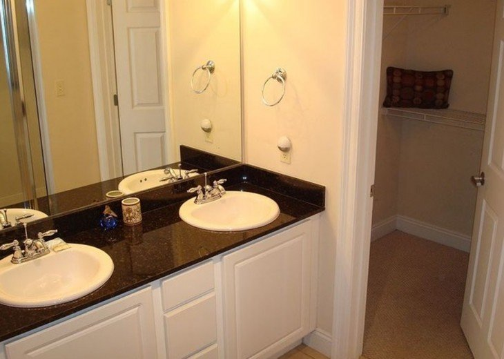 En suite has large double vanity with extra storage & walk in closet.