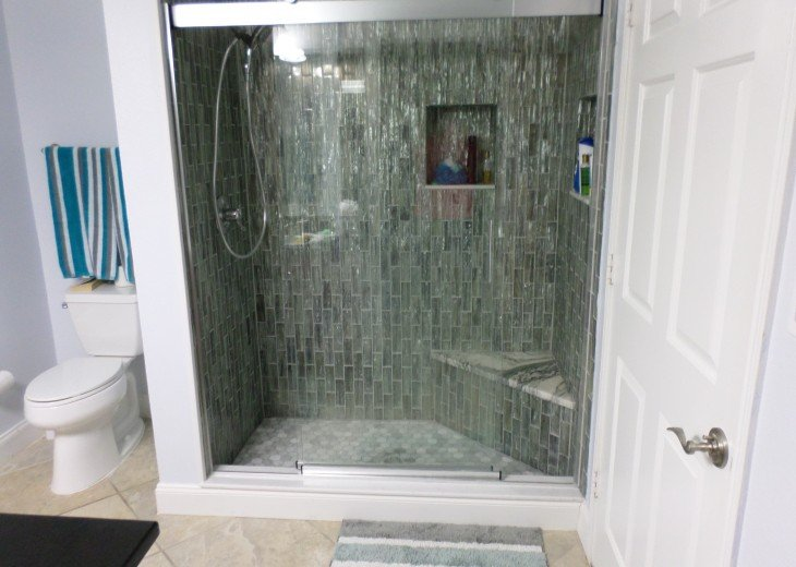 Walk in shower with corner seat, hand held shower choice.
