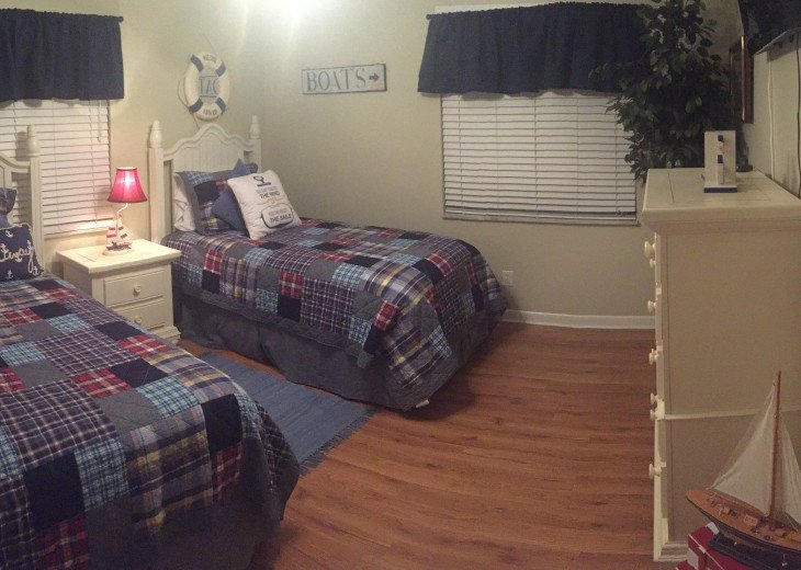 Twin bedroom with hardwood floors, TV/DVD player on wall