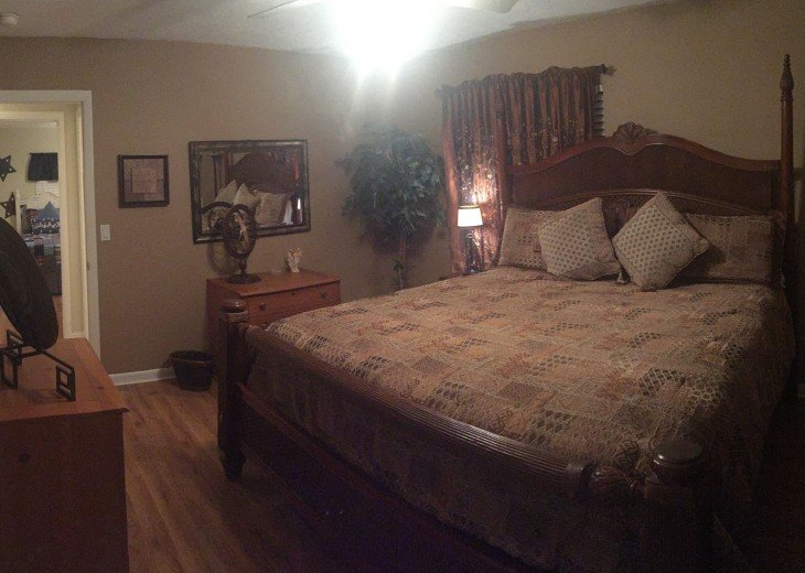 King guest bedroom with hardwood floors, ceiling fan, large closet