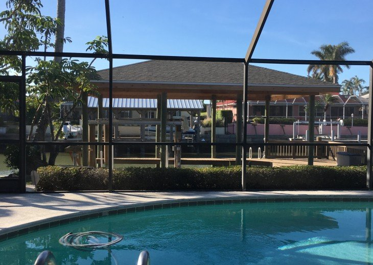 Heated pool facing pier and dock, large dining table with gas grill on deck