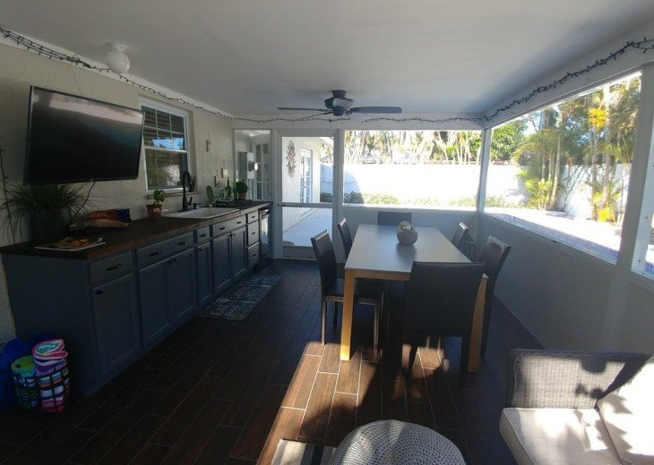 covered patio with sink, fridge and cabinets. Large table and TV
