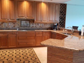 Upgraded kitchen with granite counter and tile backsplash.