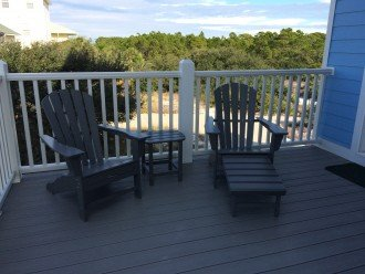 2 Adirondack chairs on deck outside dining room next to screened in porch