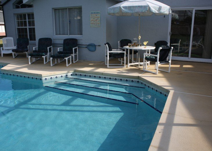 Pool and deck with patio table and chairs
