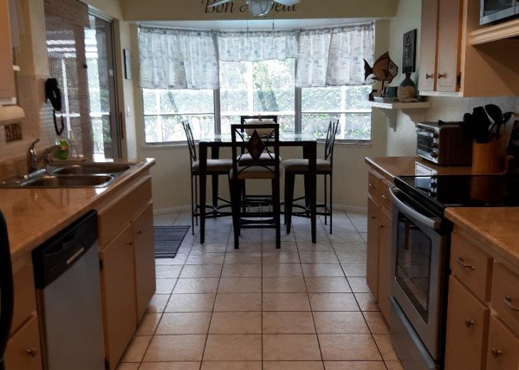 Kitchen with all amenities, sliders to pool & lanai.