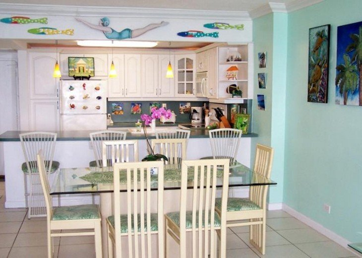 Dining Room and kitchen adorned with marine and island art.