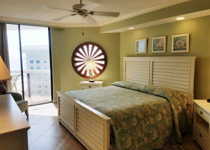 Master Bedroom King Sized Bed Ceiling Fan & a Nautical Wheel on the Window