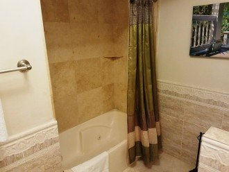 Shower/combo master bathroom with tile walls