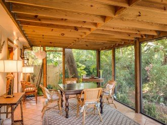 Covered, screened in patio overlooks the pool and gardens.