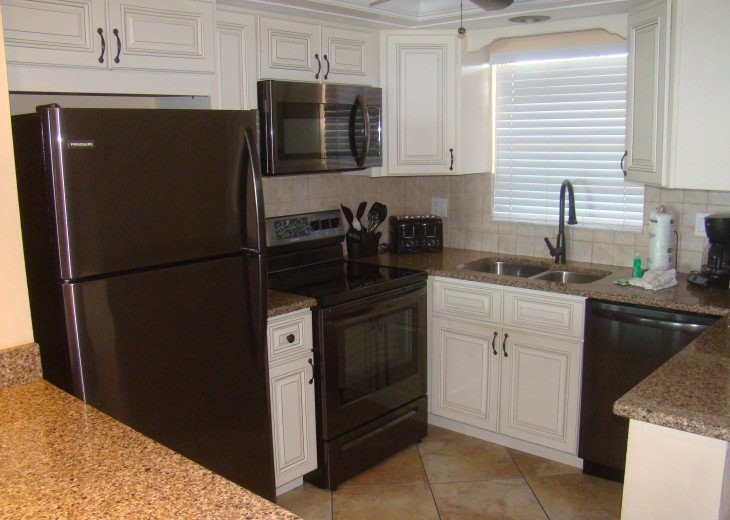 New black stainless steel appliances updated cabinets with quartz counter tops.