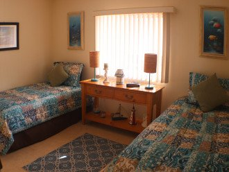 Bright and sunny bedroom with two twin beds and plenty of closet space.
