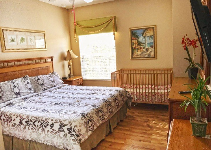 master suite with king bed and crib