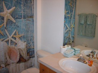 Twin bedroom private bathr with bathtub and shower.Towels and extra toilet paper