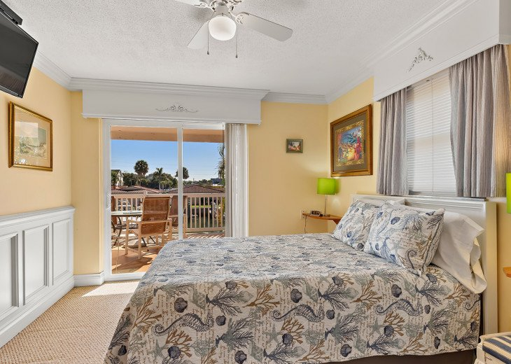 The Queen Master bedroom with wall mounted flat screen TV.