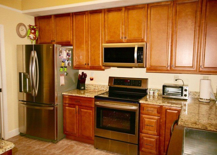 Well equipped kitchen has granite countertops and big, stainless farm sink
